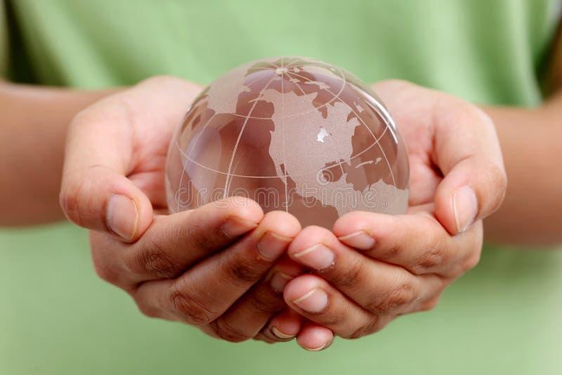 Manos que sostienen el globo de cristal fotografía de archivo libre de regalías