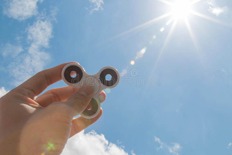 Manos que sostienen el juguete del hilandero de la persona agitada foto de archivo libre de regalías