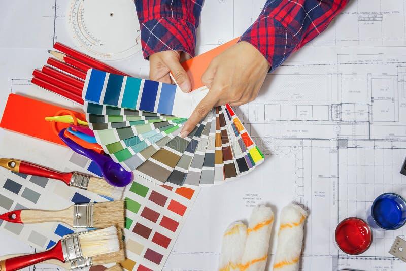 Manos que sostienen el manual abierto del entrenamiento de DIY con las herramientas del trabajo, interruptor del color imágenes de archivo libres de regalías