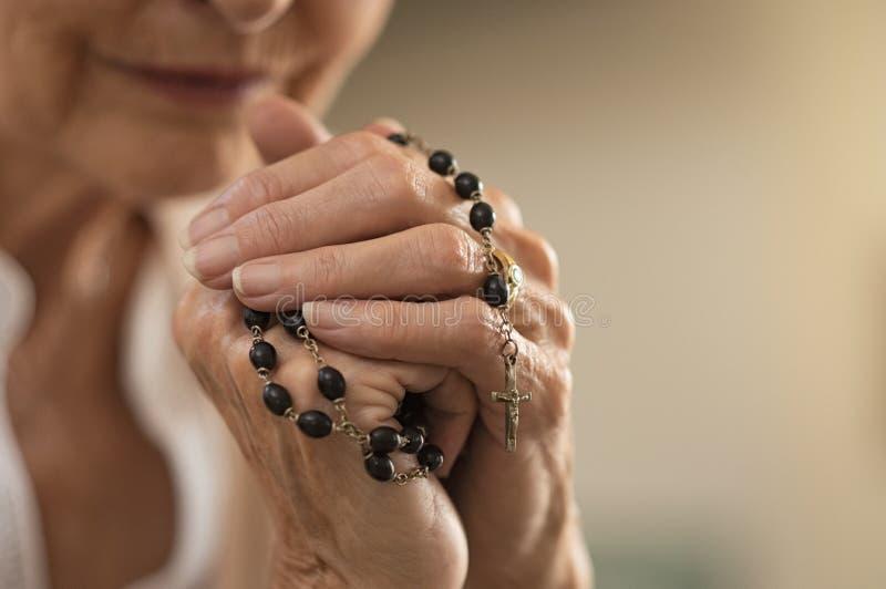 Manos que sostienen el rosario y que ruegan fotos de archivo libres de regalías
