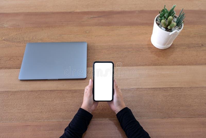 Manos que sostienen el teléfono móvil negro con la pantalla de escritorio en blanco con el pote del ordenador portátil y del cact imagen de archivo