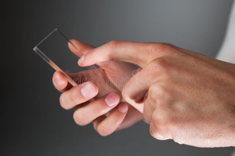 Manos que sostienen el teléfono transparente futurista imagenes de archivo