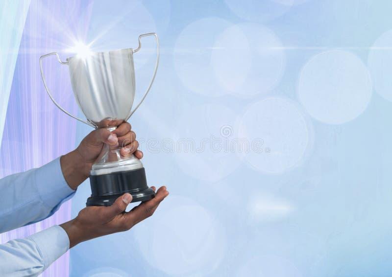 Manos que sostienen el trofeo contra fondo abstracto foto de archivo