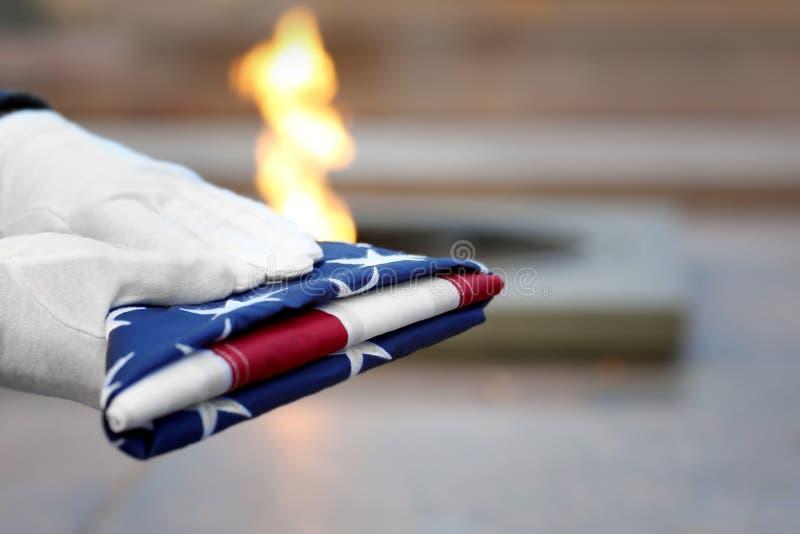 Manos que sostienen la bandera americana doblada en la llama eterna imagen de archivo