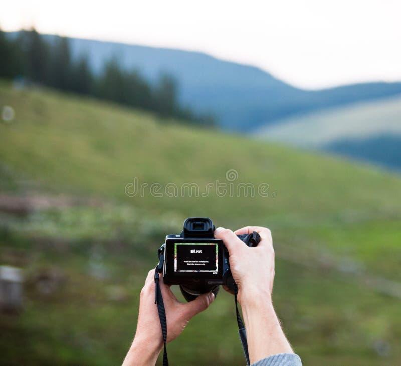 Manos que sostienen la cámara digital de la foto foto de archivo