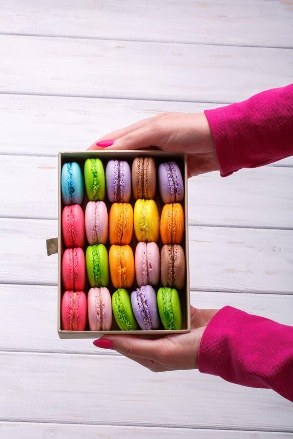 Manos que sostienen la caja de regalo con los macarrones deliciosos en el fondo de madera blanco, visión superior foto de archivo