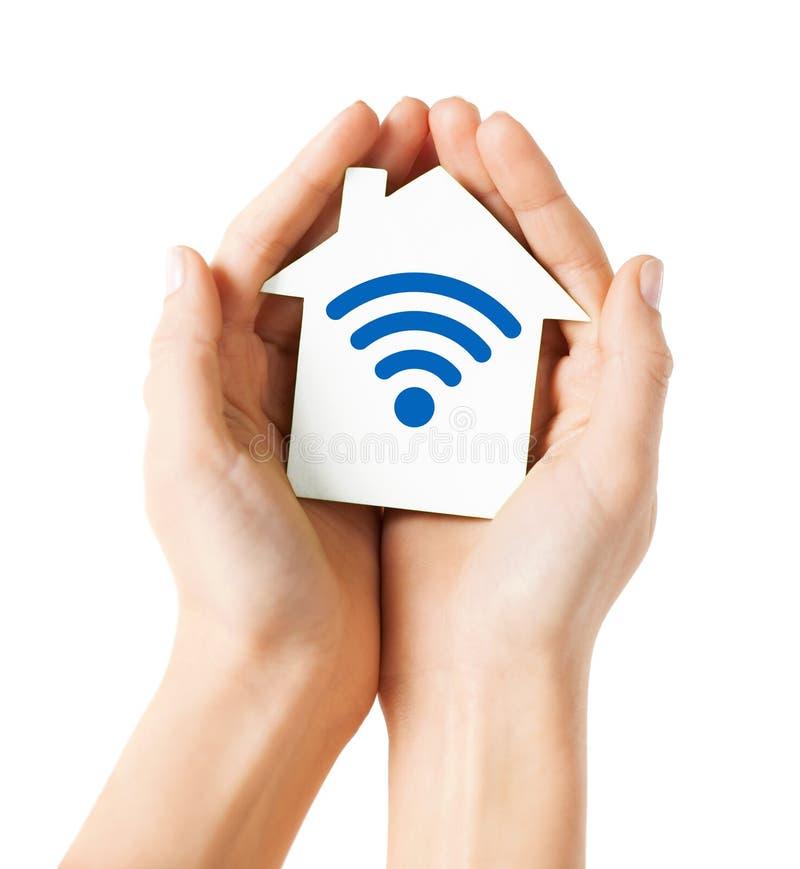 Manos que sostienen la casa con el icono de la señal de la onda de radio fotografía de archivo libre de regalías