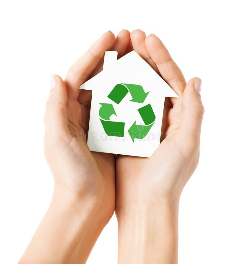 Manos que sostienen la casa con la muestra de reciclaje verde imagen de archivo libre de regalías