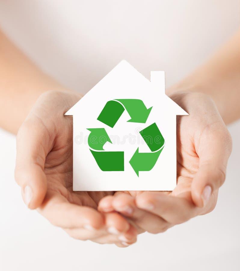 Manos que sostienen la casa con la muestra de reciclaje verde imagen de archivo