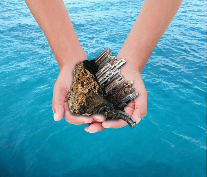 Manos que sostienen la ciudad sobre el mar imagen de archivo libre de regalías