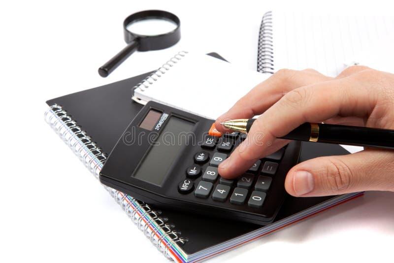 Manos que sostienen la manija y que presionan los botones de la calculadora. imagen de archivo libre de regalías