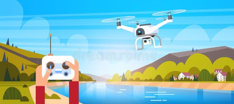Manos que sostienen la mosca de For Modern Drone del control remoto sobre fondo natural hermoso