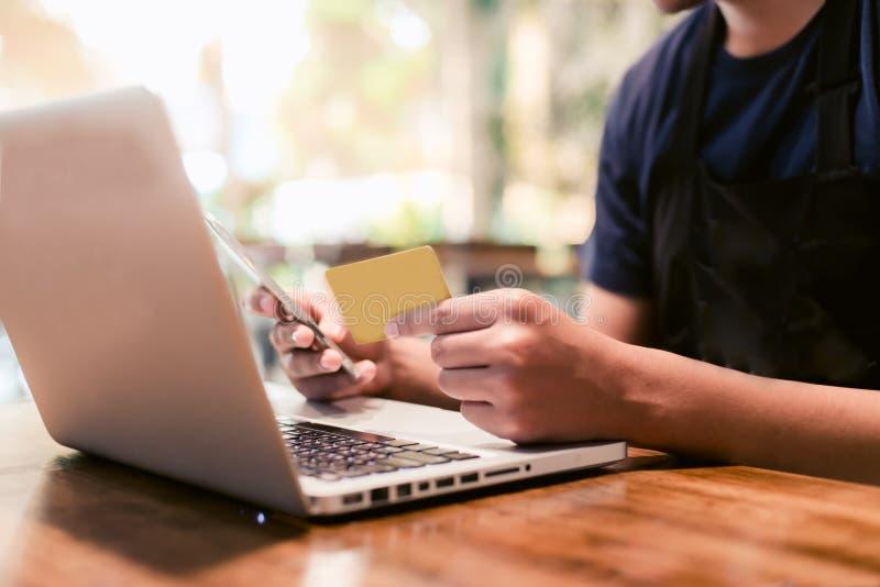 Manos que sostienen la tarjeta de crédito y que usan el ordenador portátil Compras en línea fotografía de archivo libre de regalías