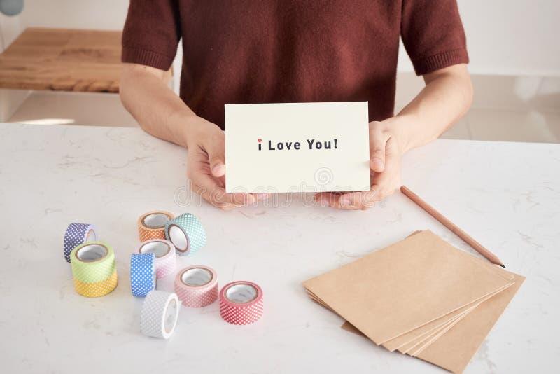 manos que sostienen la tarjeta de felicitaci?n con las letras de la frase ?te quiero ?preparadas para el amor fotografía de archivo