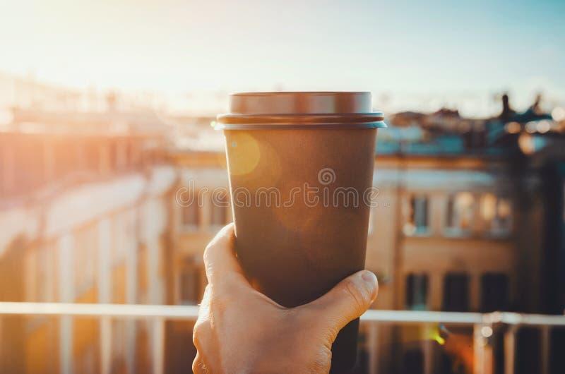 Manos que sostienen la taza caliente del arte de café o de té en luz del sol de la mañana con la visión al fondo borroso de la ci fotografía de archivo