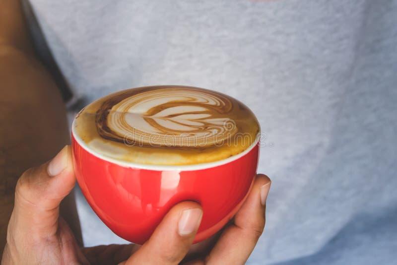 Manos que sostienen la taza de latte caliente del café con arte en forma de corazón de la espuma imagenes de archivo