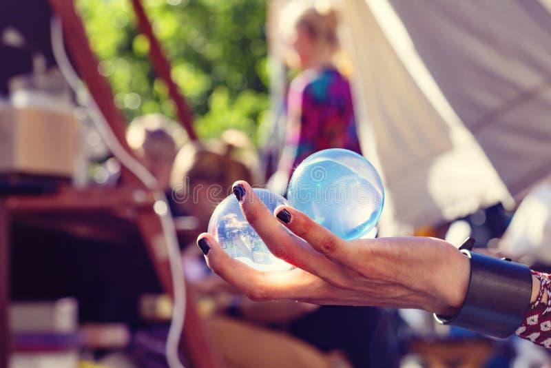 Manos que sostienen las bolas de cristal que hacen juegos malabares en el festival p?blico del verano fotografía de archivo libre de regalías