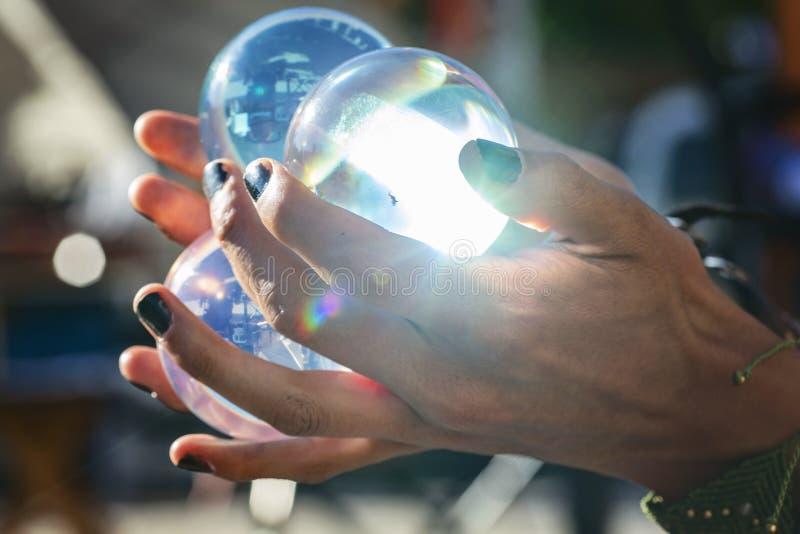 Manos que sostienen las bolas de cristal que hacen juegos malabares en el festival p?blico del verano foto de archivo libre de regalías