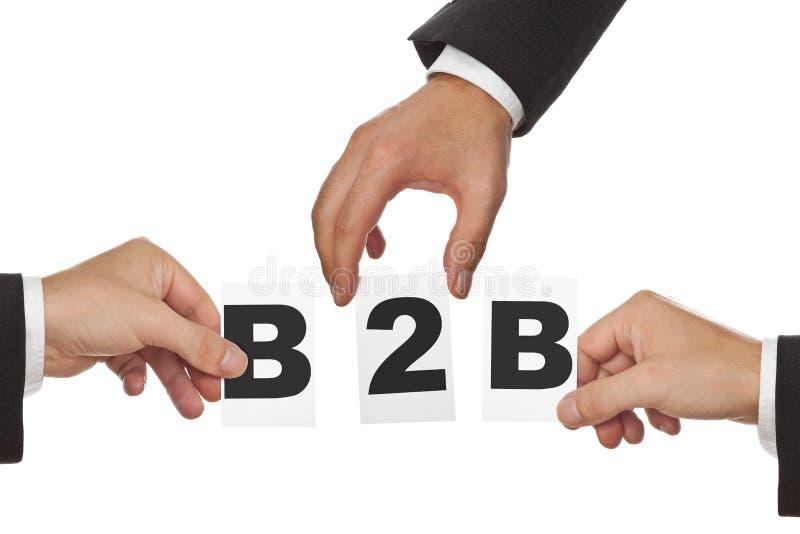 Manos que sostienen las tarjetas con las letras B2B - concepto interempresarial aisladas en blanco imagenes de archivo