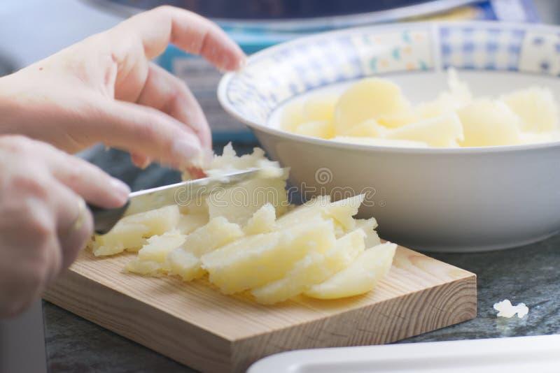 Manos que sostienen un cuchillo que corta algunas patatas en una cocina rústica espacio vac?o de la copia fotografía de archivo