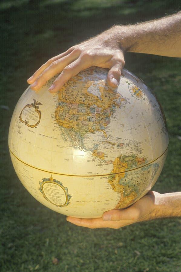 Manos que sostienen un globo sobre un remiendo de la hierba imagenes de archivo
