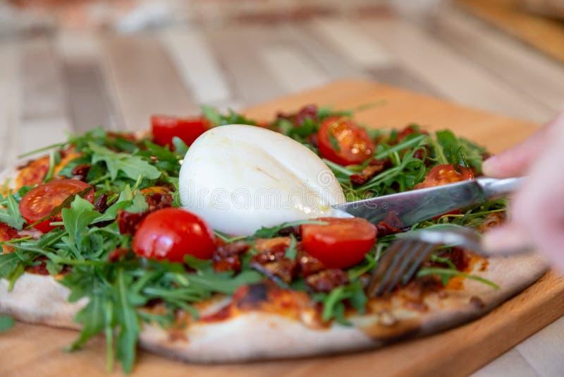 Manos que sostienen una bifurcación y un cuchillo que cortan el queso de una pizza en un tablero de madera fotos de archivo libres de regalías