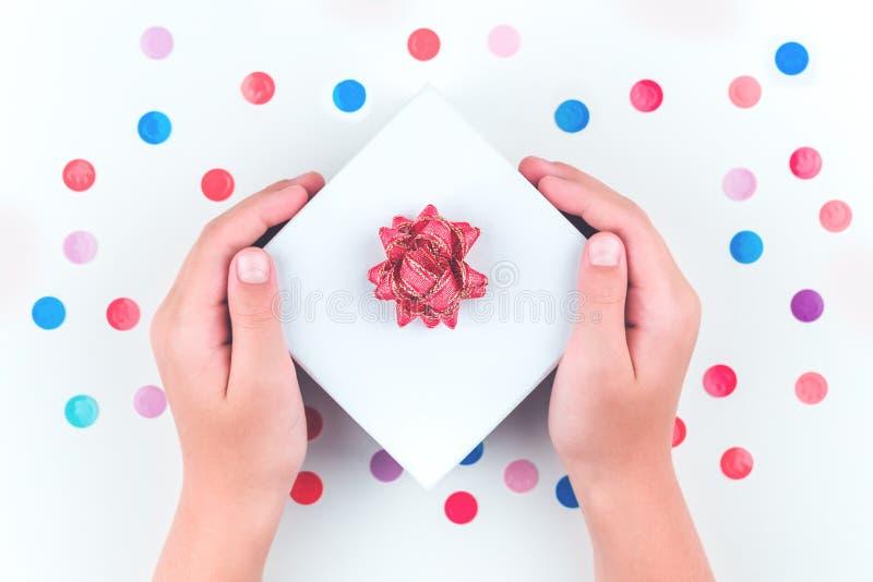 Manos que sostienen una caja de regalo sobre confeti foto de archivo