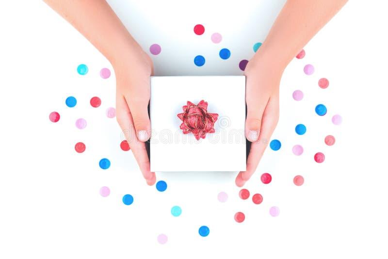 Manos que sostienen una caja de regalo sobre confeti imagenes de archivo