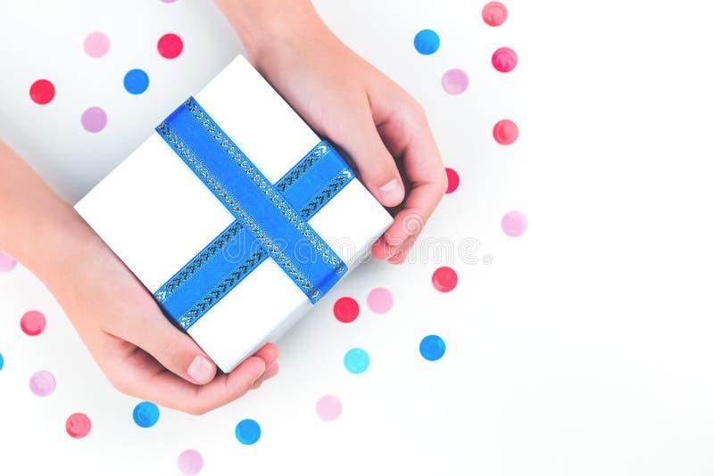 Manos que sostienen una caja de regalo sobre confeti imagen de archivo libre de regalías