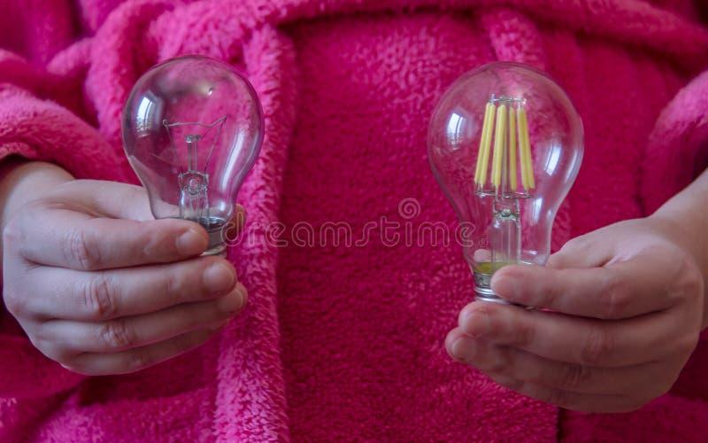 Manos que sostienen una nueva bombilla en el LED y la lámpara incandescente La opción entre la economía y la eficacia foto de archivo