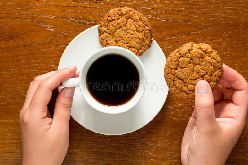 Manos que sostienen una taza de café y de galletas imágenes de archivo libres de regalías