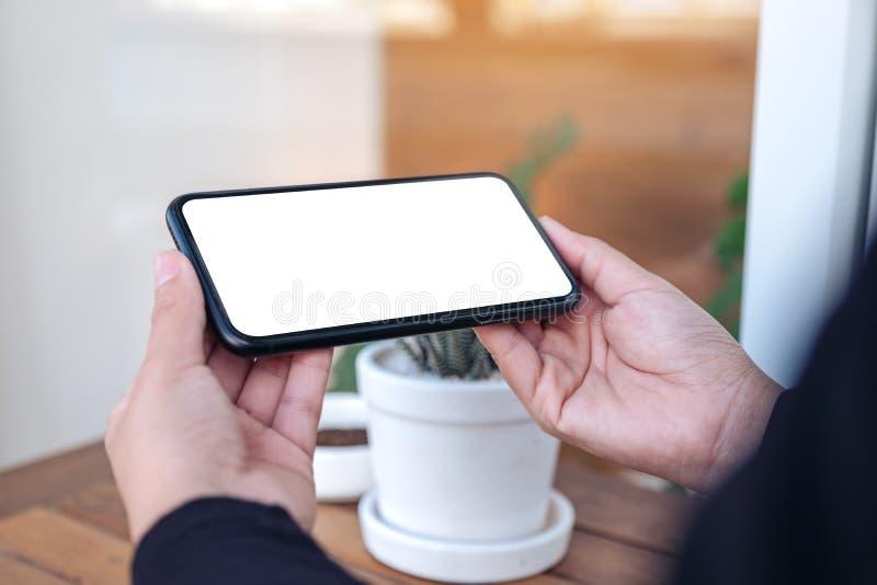 Manos que sostienen y que usan un teléfono móvil negro con la pantalla en blanco horizontalmente para mirar en el aire libre fotografía de archivo libre de regalías