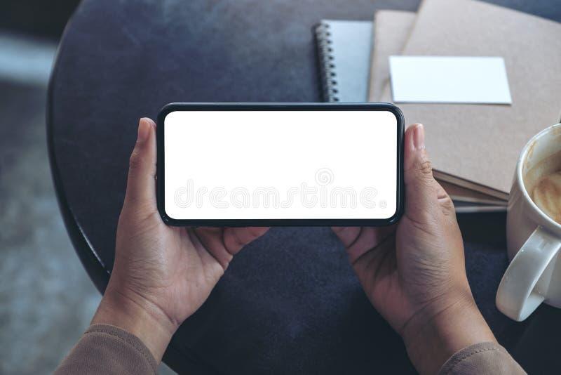 Manos que sostienen y que usan un teléfono móvil negro con la pantalla en blanco horizontalmente para mirar con la taza y los cua fotografía de archivo