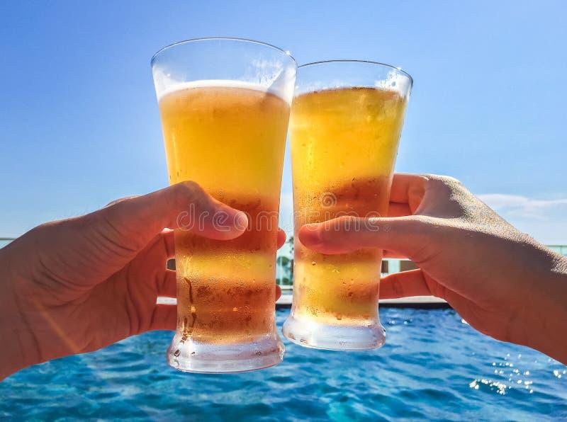 Manos que tintinean los vidrios de cerveza por la piscina foto de archivo