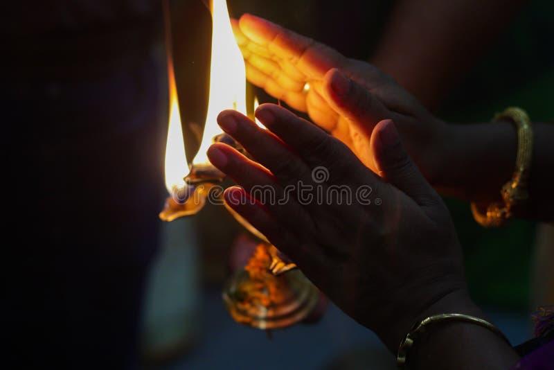 Manos que toman calor de la llama santa del diya divino del puja hindú de la adoración de dios para las bendiciones imagen de archivo