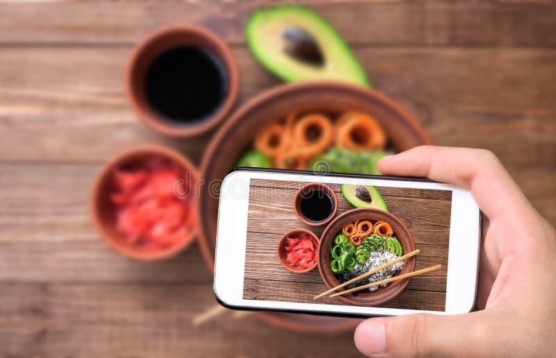 Manos que toman el cuenco del sushi de la foto con smartphone fotografía de archivo libre de regalías