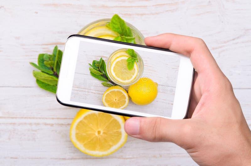 Manos que toman la bebida del limón de la foto con smartphone imagen de archivo