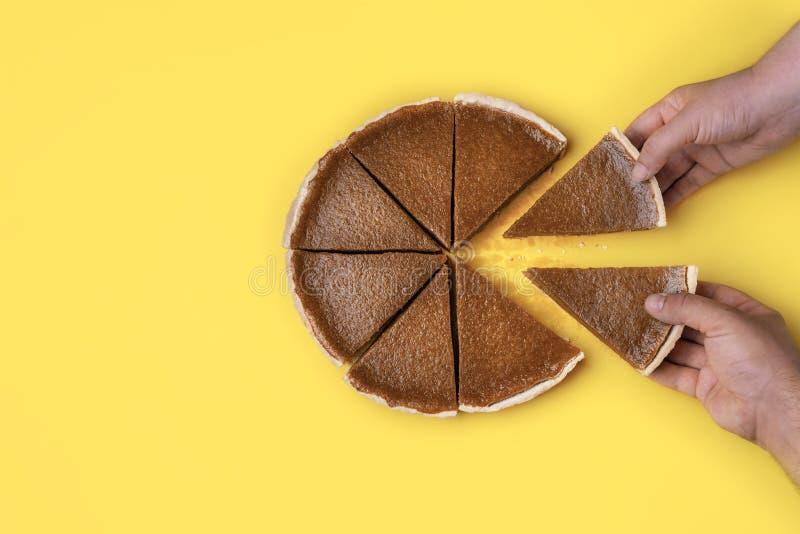Manos que toman rebanadas de la empanada Consumici?n de la empanada de calabaza fotografía de archivo