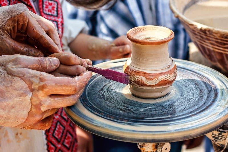 Manos que trabajan en la rueda de la cerámica Escultor, alfarero Manos humanas que crean un nuevo pote de cerámica foto de archivo