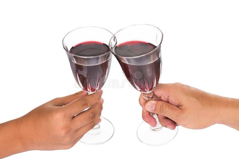 Manos que tuestan el vino rojo en cristales fotos de archivo