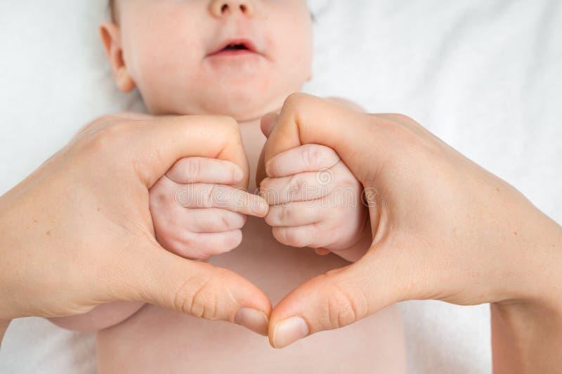 Manos recién nacidas de la madre de la tenencia del bebé en forma del corazón imagenes de archivo