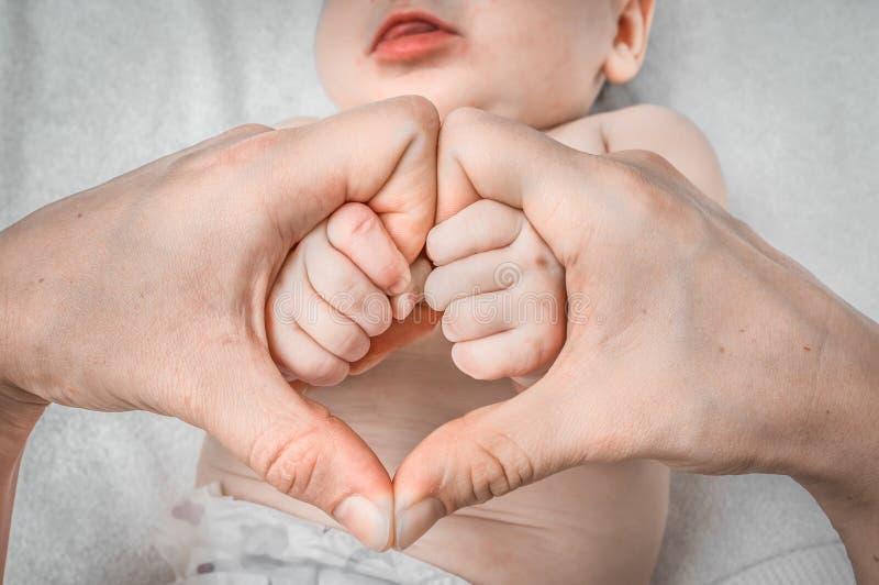 Manos reci?n nacidas de la madre de la tenencia del beb? en forma del coraz?n imagenes de archivo