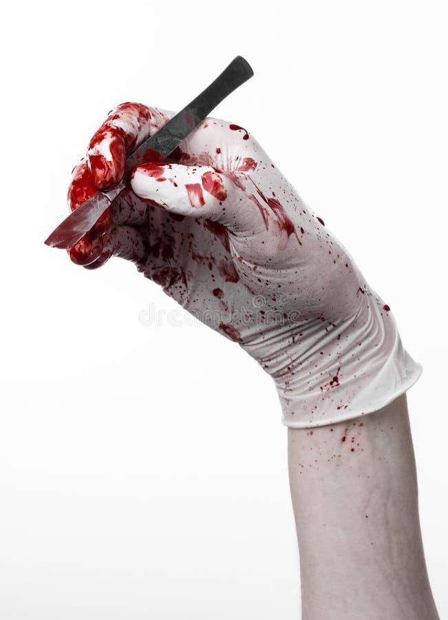 Manos sangrientas en guantes con el escalpelo, fondo blanco, aislado, doctor, asesino, maniaco fotografía de archivo