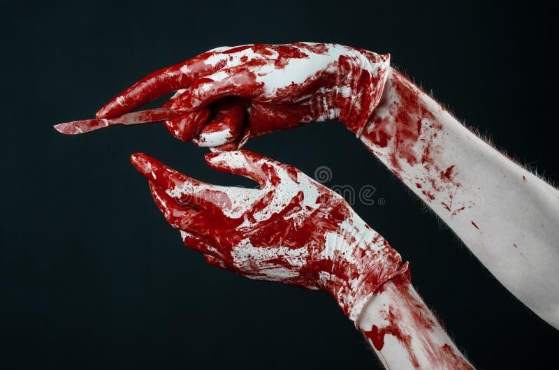 Manos sangrientas en los guantes blancos, un escalpelo, un clavo, fondo negro, zombi, demonio, maniaco fotos de archivo