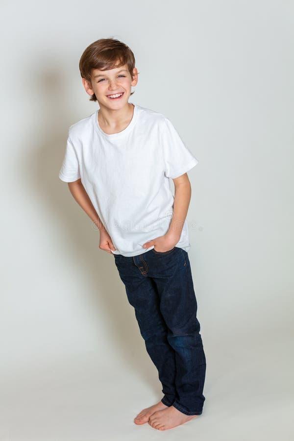 Manos sonrientes del muchacho feliz joven en los bolsillos que llevan vaqueros azules del dril de algodón imágenes de archivo libres de regalías