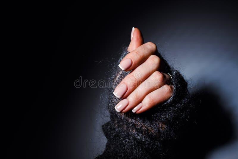 Manos suaves femeninas con la manicura francesa hermosa fotos de archivo