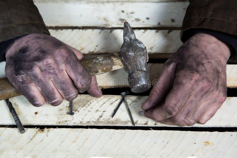Manos sucias de trabajadores con los martillos y los clavos de las herramientas fotos de archivo libres de regalías