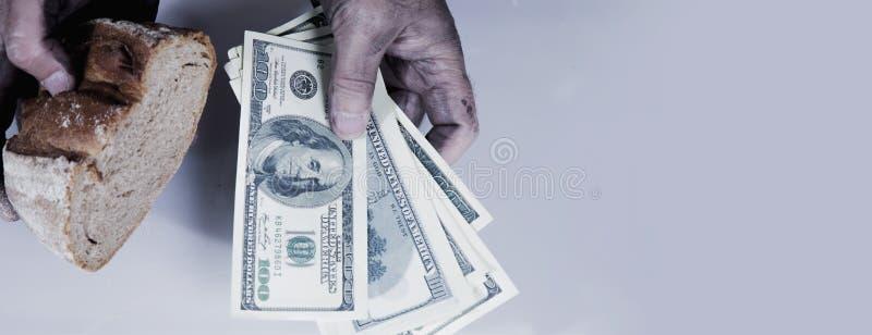 Manos sucias del hombre con el pedazo de pan y de dinero como símbolo de la pobreza, alto coste de comida Foco selectivo en cuent foto de archivo