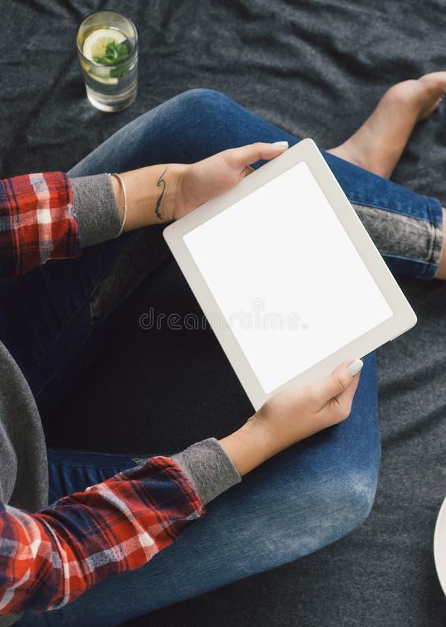 Manos superiores de la mujer que sostienen la cama que se sienta vacía de la pantalla en blanco de la tableta fotografía de archivo libre de regalías