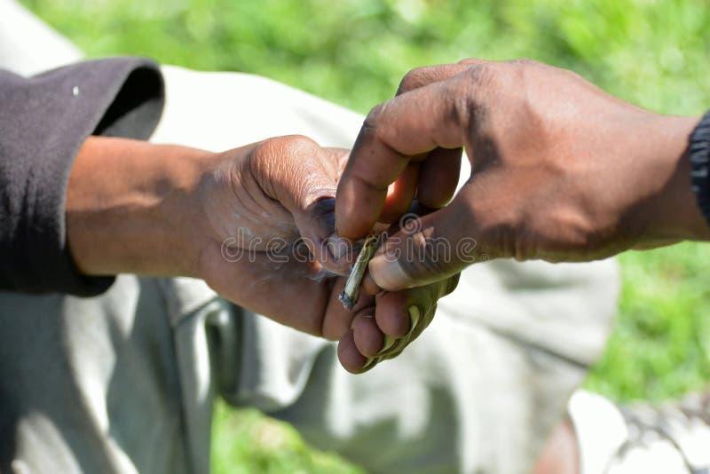 Manos surafricanas que intercambian el cigarrillo foto de archivo libre de regalías